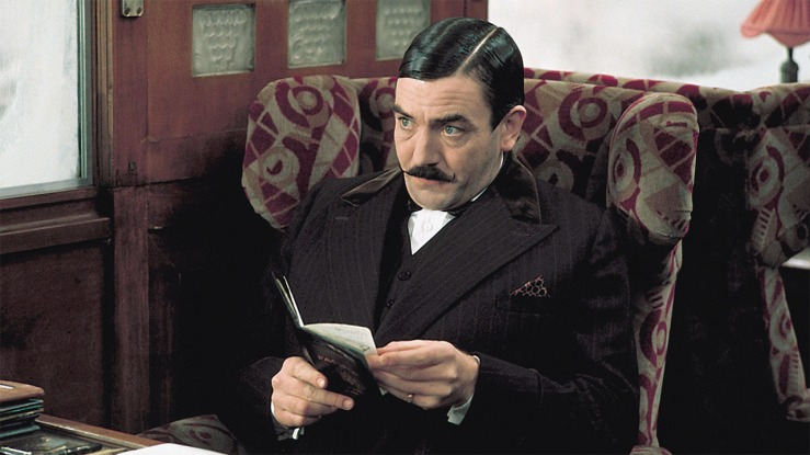 Hercule Poirot reads a passport in Murder on the Orient Express