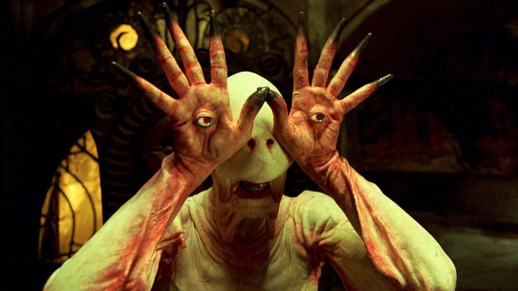 A pale monster with eyes in its hands gets a good look at Ofelia in Pan's Labyrinth