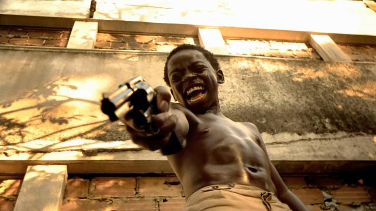 A Brazilian boy grimaces and aims his gun in City of God