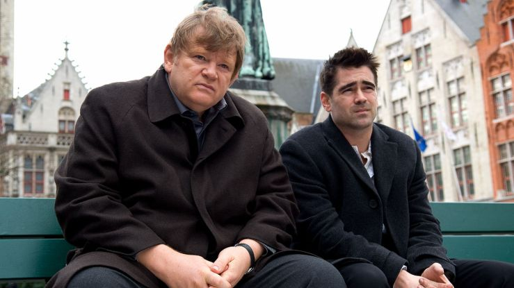 Ken and Ray sit on a bench in In Bruges