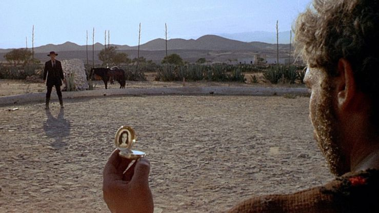 El Indio holds a pocket watch and stands off against Colonel Douglas Mortimer in For a Few Dollars More