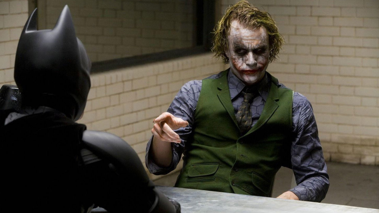 Batman and the Joker sit across a table from each other in The Dark Knight