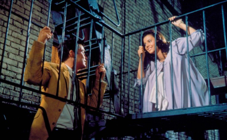 Tony and Maria, sitting on a fire escape, share a romantic moment in West Side Story