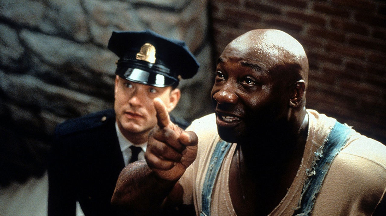 Paul Edgecomb and John Coffey look at something offscreen in The Green Mile