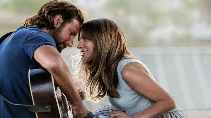 Ally gazes lovingly at Jackson as he plays guitar in A Star is Born