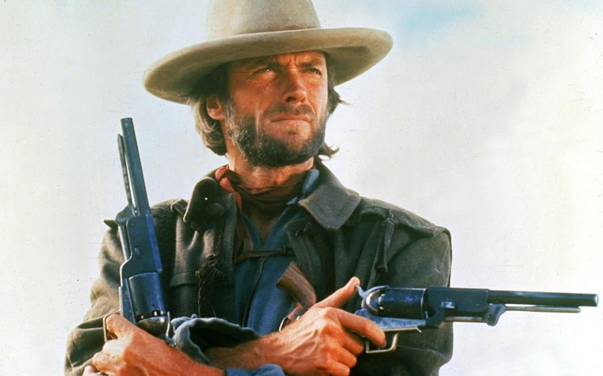 Josey Wales looks stoic with two pistols in The Outlaw Josey Wales