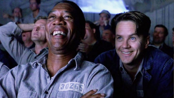 Red and Andy smile as the watch a movie in The Shawshank Redemption
