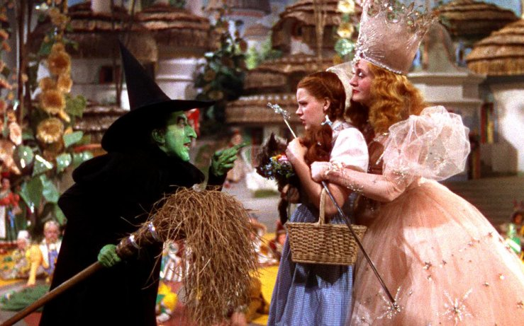 The Wicked Witch points menacingly at Dorothy as she's held by the Good Witch Glinda