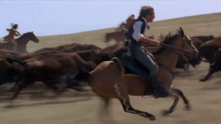 John Dunbar and a Sioux tribe member ride their horses alongside a herd of wild buffalo