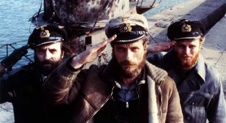 Three German soldiers standing in front of a u-boat salute the camera