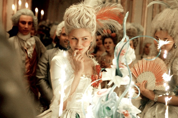 Marie Antoinette playfully tastes cake frosting off of her fingertip in the 2006 film